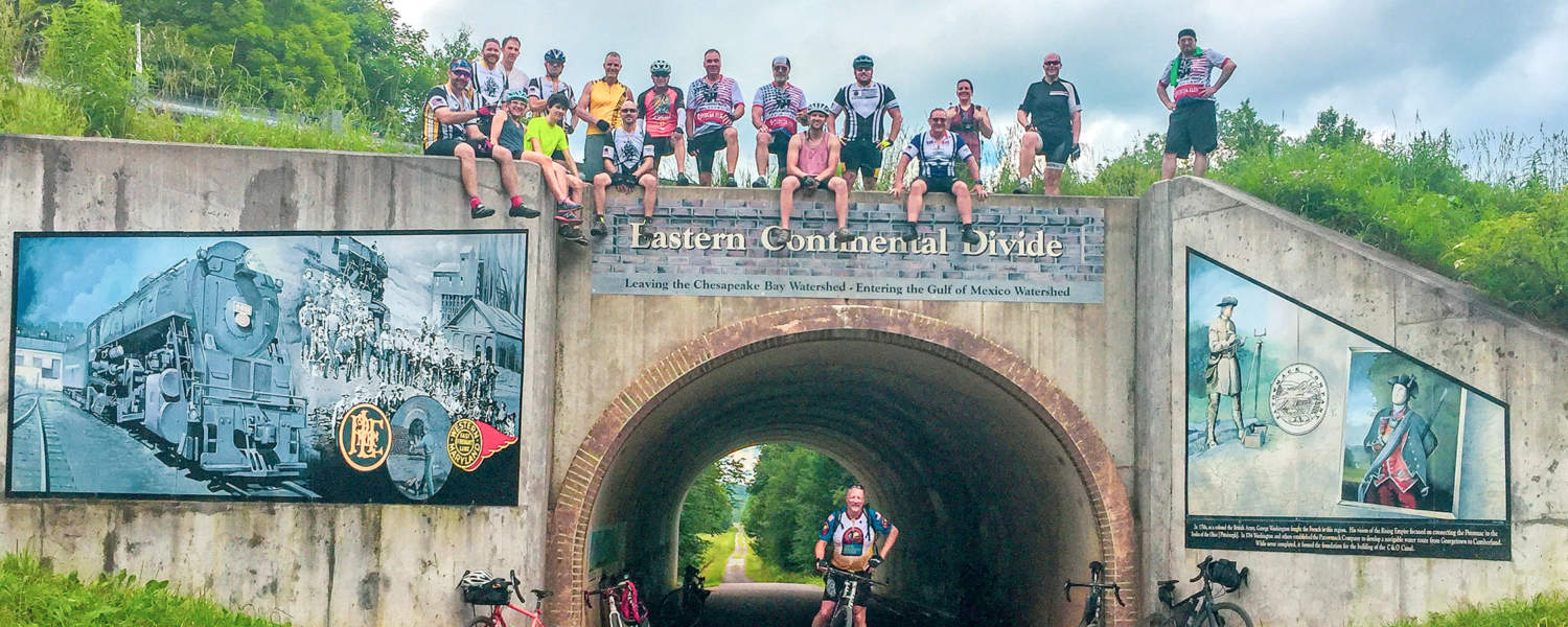 Cyclists on top of Eastern Continental Divide Landmark