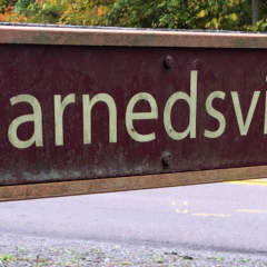 Harnedsville sign on fence